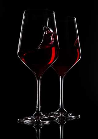 Glasses of red wine with reflection on black background