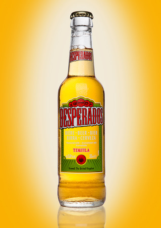 LONDON, UK - JANUARY 02, 2017: Bottle of Desperados beer on yellow background, lager flavored with tequila is a popular beer produced by Heineken and sold in over 50 countries around the world.