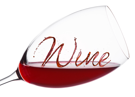 Glass of red wine with wine font splash and drops on white background Stock Photo