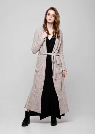 knitwear: Young beautiful fashion model wearing knitwear  dress on grey background