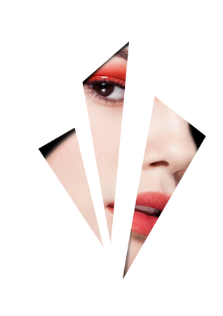 Beauty red eyes and lips makeup fashion model on black background looking through three white triangles. Creative artwork Stock Photo