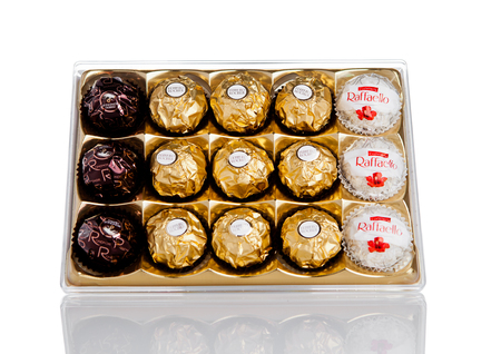 ferrero: LONDON, UK - FEBRUARY 28, Ferrero Collection Rocher premium chocolate sweets plastic box.On white background with reflection.