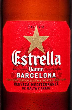 LONDON,UK - MARCH 21, 2017 : Bottle label of Estrella Damm beer on white background with reflection, Estrella Damm is a pilsner beer, brewed in Barcelona.