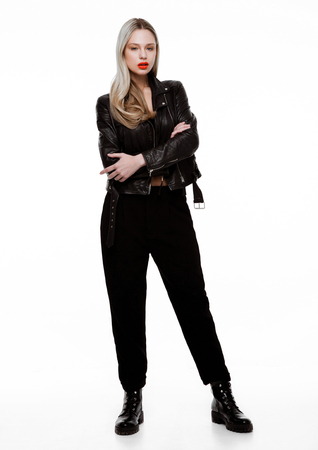 Rockstar biker fashion model girl wearing leather jacket. Long blond hair abd red lips. Studio shot on white background