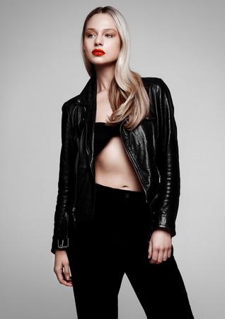 ロックスター バイカー ファッション モデルの女の子が革のジャケットを身に着けています。長いブロンドの髪・ アブド ・赤い唇。灰色の背景で撮