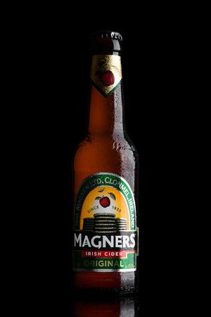 illustrative editorial: LONDON, UK - JUNE 9, 2017: Bottle Of Magners Original Irish Cider on a Black Background Editorial