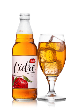 LONDON, UNITED KINGDOM - JUNE 22, 2017: Bottle and glass with ice cubes of Stella Artois Cidre Apple Cider on white background.