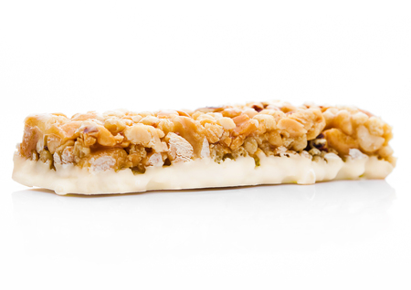 Caramel protein cereal energy bar with nuts on white background