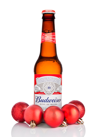 LONDON, UK - OCTOBER 14, 2017:: Bottle of Budweiser Beer on white background with christmas decoration balls, an American lager first introduced in 1876.
