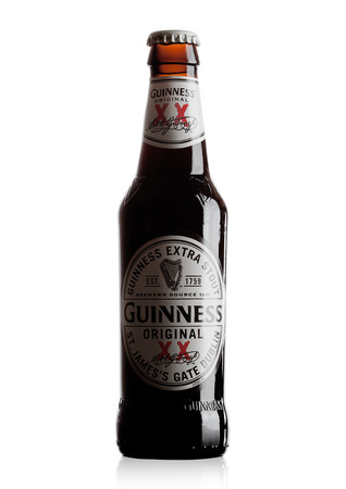 LONDON, UK - OCTOBER 15, 2017: Guinness extra stout beer bottle on white background. Guinness beer has been produced since 1759 in Dublin, Ireland. Editorial