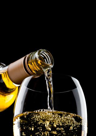 52637a1030b33d  88792596 - Gietende witte die wijn van fles aan glas op zwarte achtergrond  wordt geïsoleerd