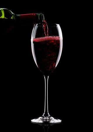 65b9e3d1adc8d3  88792601 - Gieten van rode wijn van fles naar glas geïsoleerd op zwarte  achtergrond