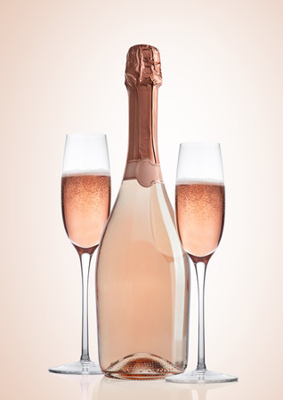 Bottle and glasses of pink rose champagne on pink background