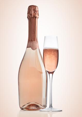 Fles en glas roze roze champagne op roze achtergrond Stockfoto - 89345615