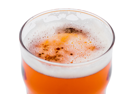 Beer in glass with foam. View from above on white background