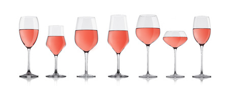 Glasses of rose pink wine on white background with reflection