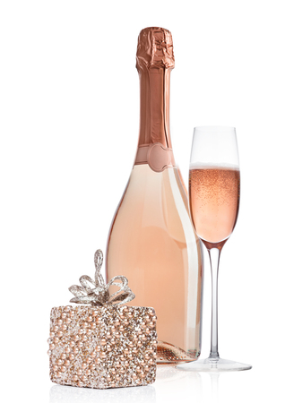 Bottle and glass of pink rose champagne with christmas decoration and gift on white background Standard-Bild