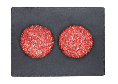 Raw fresh beef burgers on stone plate on white background Stock Photo