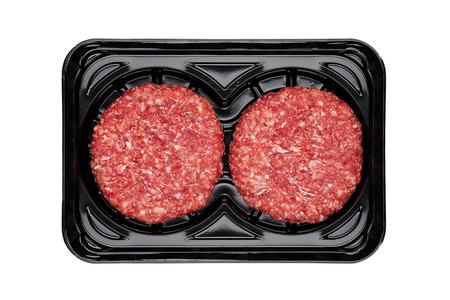 Raw fresh beef burgers in plastic tray on white background Foto de archivo