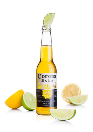 LONDON, UK - November 24, 2017: Bottle of Corona Extra Beer with lime slice and lemons.Corona, produced by Grupo Modelo with Anheuser Busch InBev, is the most popular imported beer in the US.