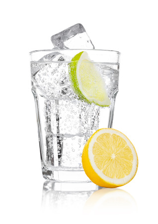 Glass of sparkling water soda drink lemonade with ice and lime lemon slice on white background Stock Photo