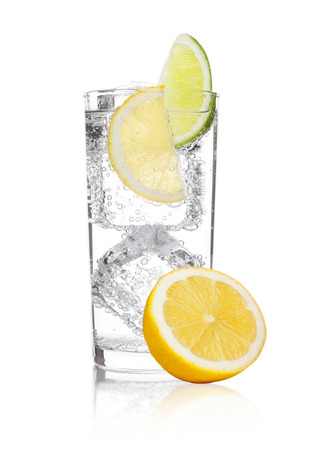 Glass of sparkling water soda drink lemonade with ice and lime lemon slice on white background Foto de archivo