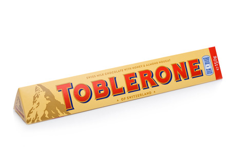LONDON, UK -DECEMBER 07, 2017: Toblerone Swiss Milk Chocolate with Honey and Almond Nougat on white background. Toblerone is a Swiss chocolate.