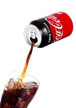LONDON, UK - JANUARY 02, 2018: Pouring Coca Cola Zero soda drink from aluminium tin to glass on white background. The drink is produced and manufactured by The Coca-Cola Company. Редакционное