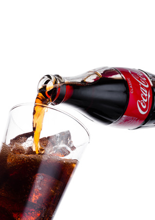 LONDON, UK - JANUARY 02, 2018: Pouring Coca Cola soda drink from bottle to glass on white background. The drink is produced and manufactured by The Coca-Cola Company. Editorial