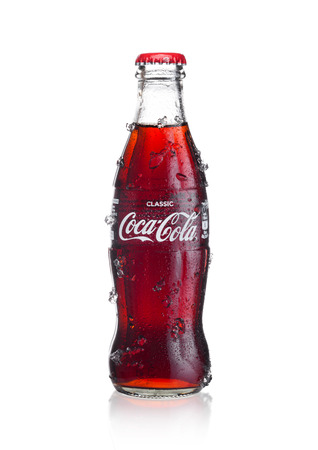 LONDON, UK - JANUARY 02, 2018: Cold glass bottle of Coca Cola drink  with ice and dew on white background. The drink is produced and manufactured by The Coca-Cola Company.