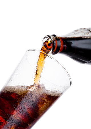 Pouring cola soda drink from bottle to glass  with ice cubes on white background Stock fotó