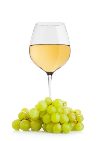 Glass of white wine with green grapes on white background Standard-Bild