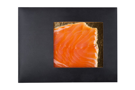 Black paper package with raw fresh salmon slices on white background