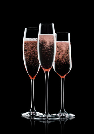 Rose pink champagne glasses with bubbles on black background with reflection