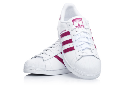 LONDON, UK - JANUARY 12, 2018: Adidas Originals Superstar red shoes on white background.German multinational corporation that designs and manufactures sports shoes, clothing and accessories. Editorial