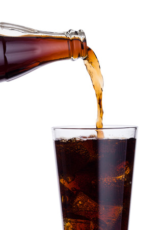 Pouring cola soda drink from bottle to glass  with ice cubes on white background Archivio Fotografico