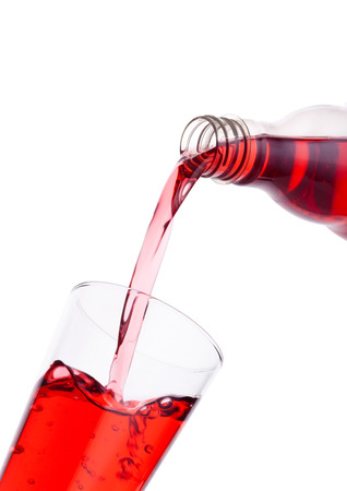 Pouring cranberry red juice from bottle to glass  on white background