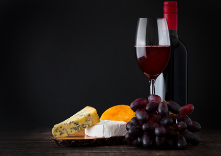 Bottle and glass of red wine with cheese selection with grapes on black background Standard-Bild