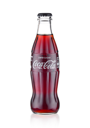 LONDON, UK - JANUARY 20, 2018: Cold glass bottle of Zero Coca Cola drink  on white background. The drink is produced and manufactured by The Coca-Cola Company.
