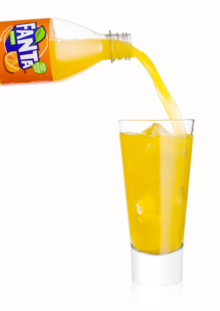 LONDON, UK - JANUARY 20, 2018: Pouring Fanta soft drink from bottle to glass on white background. Fanta is popular fruit-flavored carbonated soft drink created by Coca-Cola company. Editorial
