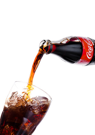 LONDON, UK - JANUARY 20, 2018: Pouring Coca Cola soda drink from bottle to glass on white background. The drink is produced and manufactured by The Coca-Cola Company. Redakční