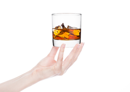 Female hand holding whiskey glass with ice on white background.