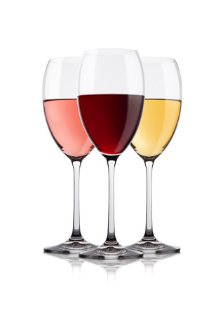 Elegant glasses of white red and pink rose wine on white background