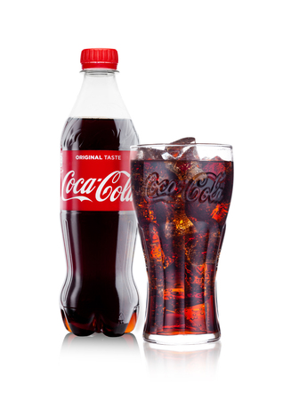 LONDON, UK - JANUARY 24, 2018: Bottle and glass of Classic Coca-Cola on white Background. Coca-Cola is one of the most popular soda products in the world. Editorial