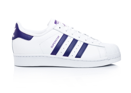 LONDON, UK - JANUARY 24, 2018: Adidas Originals Superstar blue shoes on white background.German multinational corporation that designs and manufactures sports shoes, clothing and accessories. Editorial