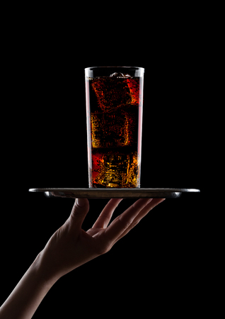 Hand holds tray with glass of cola soda with ice cubes on black background Stock Photo