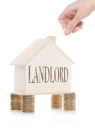 Wooden house model standing on coins and hand holding the coin with conceptual text. Landlord