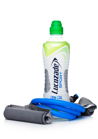 LONDON, UK - FEBRUARY 02, 2018: Bottle of Lucozade low calories sport energy soda drink with resistance band on white background. Editorial