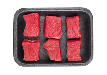 Pieces of fresh raw beef meat in plastic tray on white background Banco de Imagens