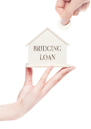 Female hand holds wooden house model and hand holding the coin with conceptual text. Bridging loan